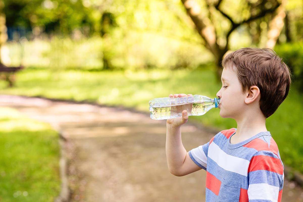 boy drinking mineral water from the plastic bottle